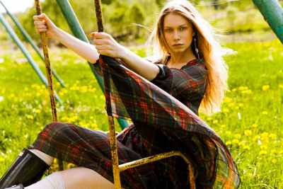 Girl wearing fashion dress swings on a swing at green park