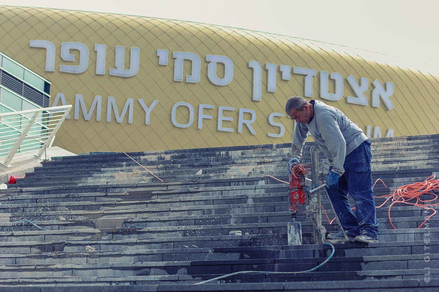 A man drilling through concrete stairs