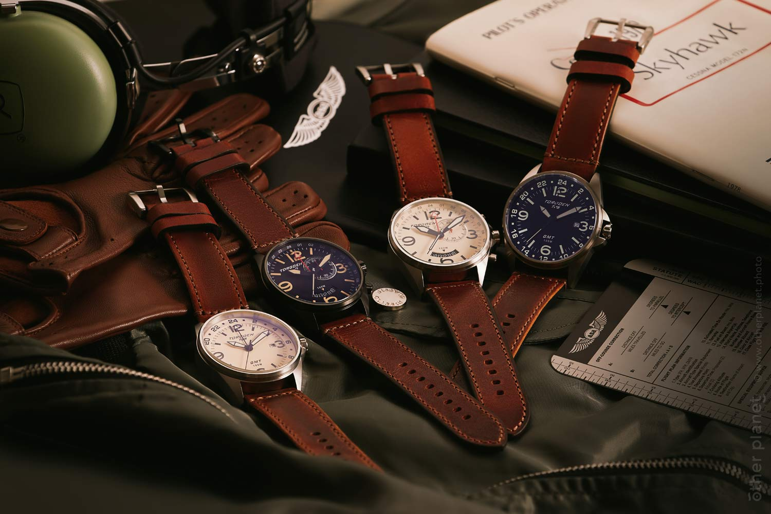 Arrangement of four Torgoen pilot watches with props