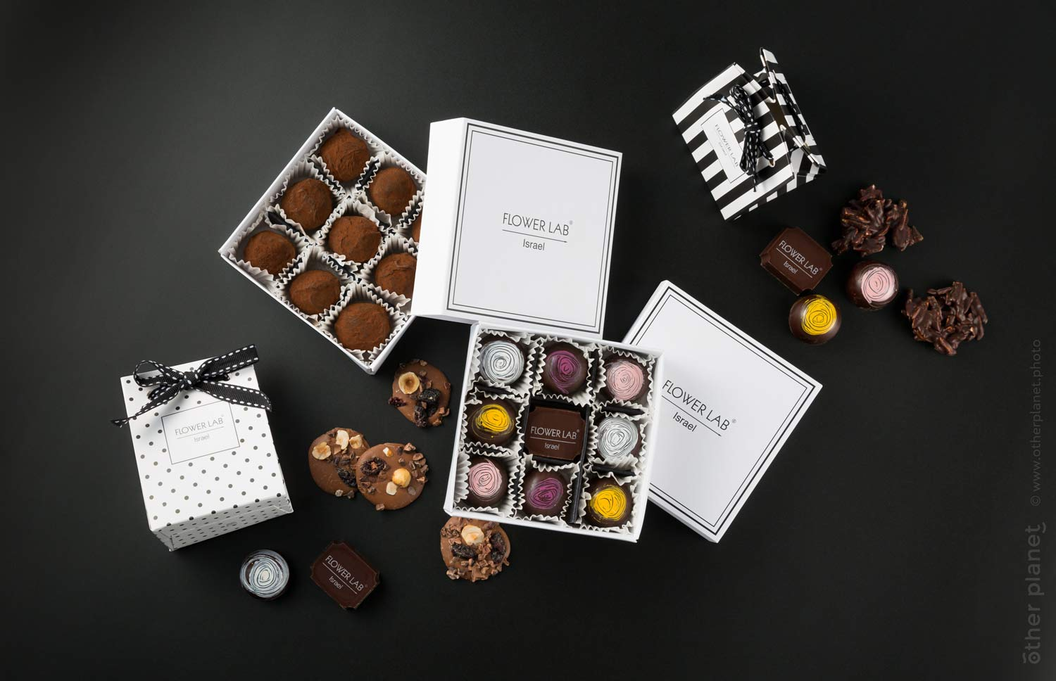 Chocolate sweets and packages branded with Flowerlab logo on black background