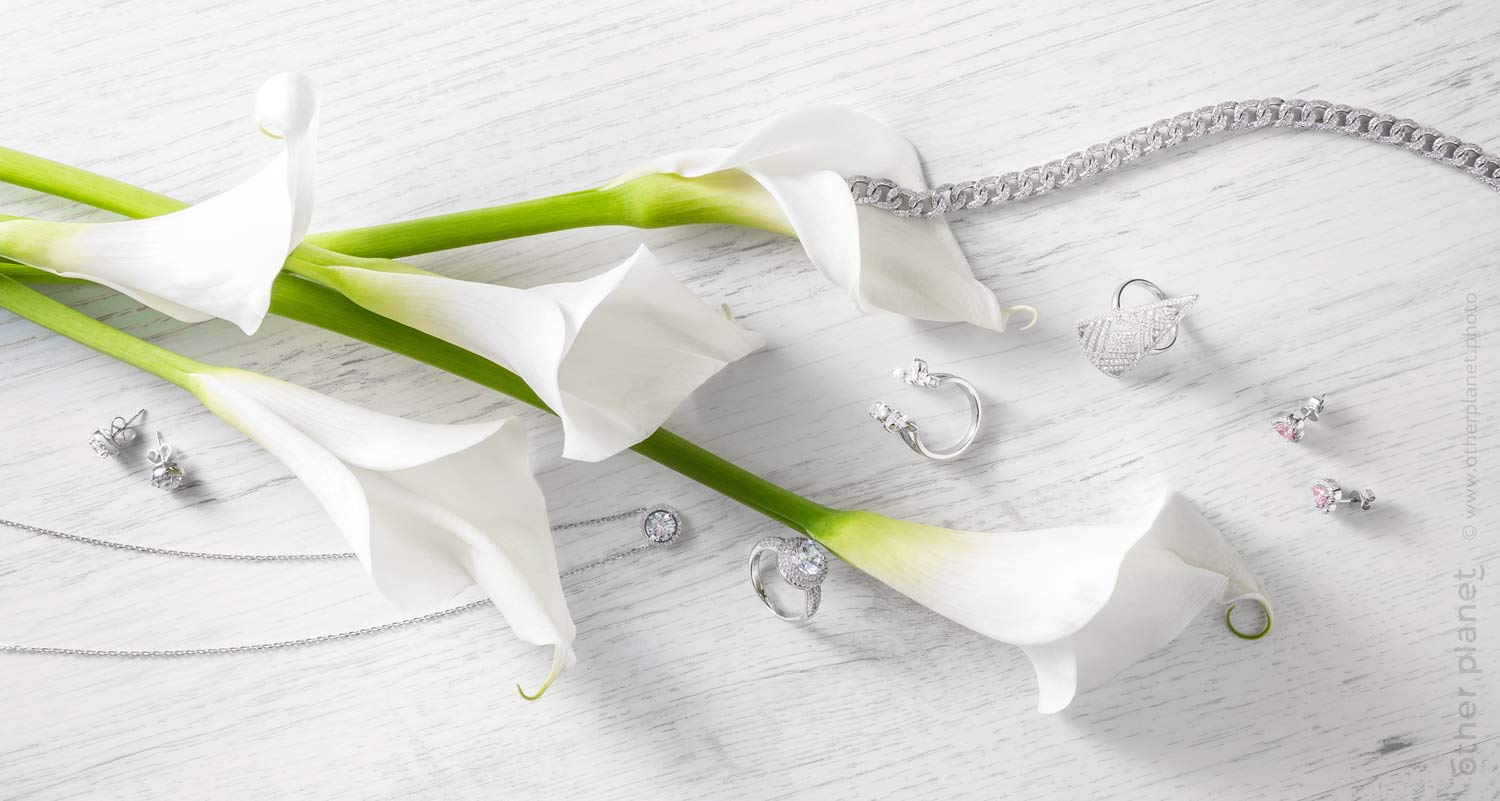 Composition of jewelry with callas flowers on bright wooden table - top view