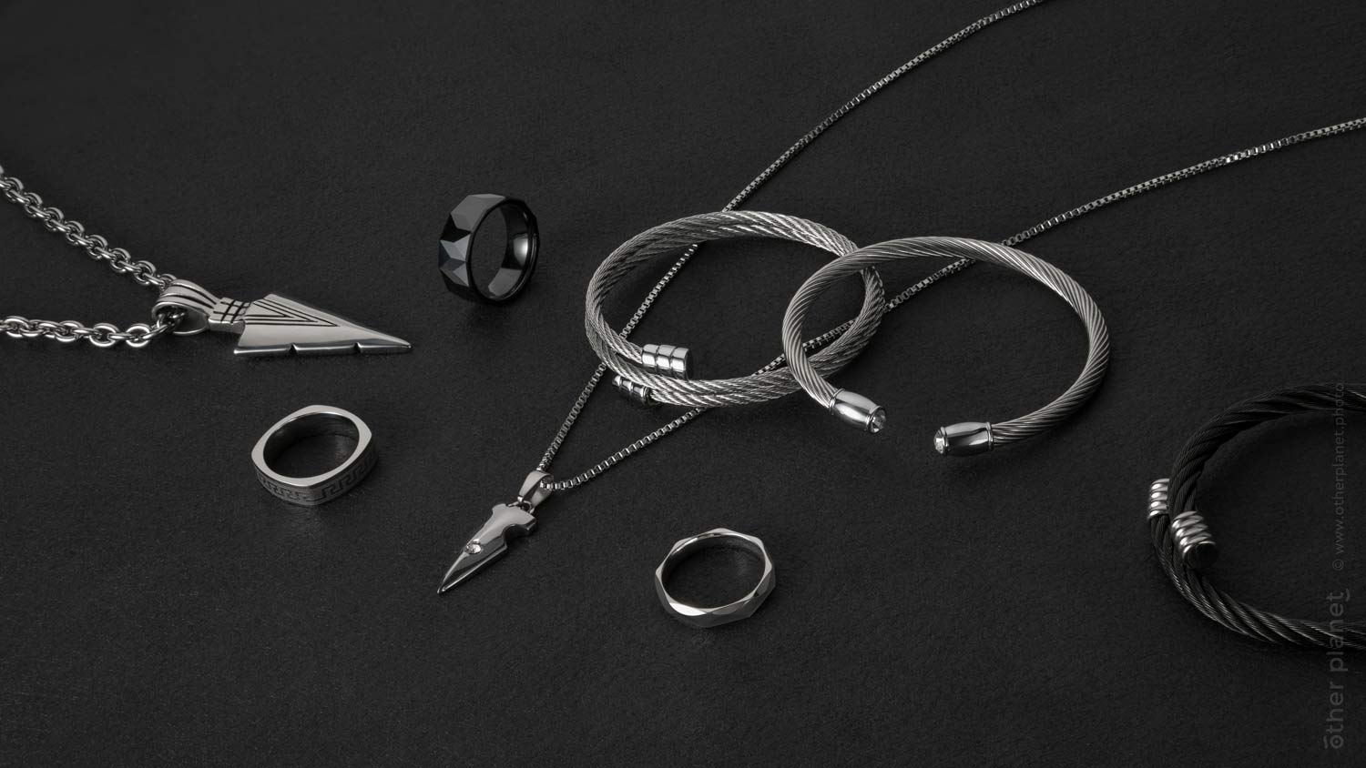 Jewelry for men collection arrangement on plain black background