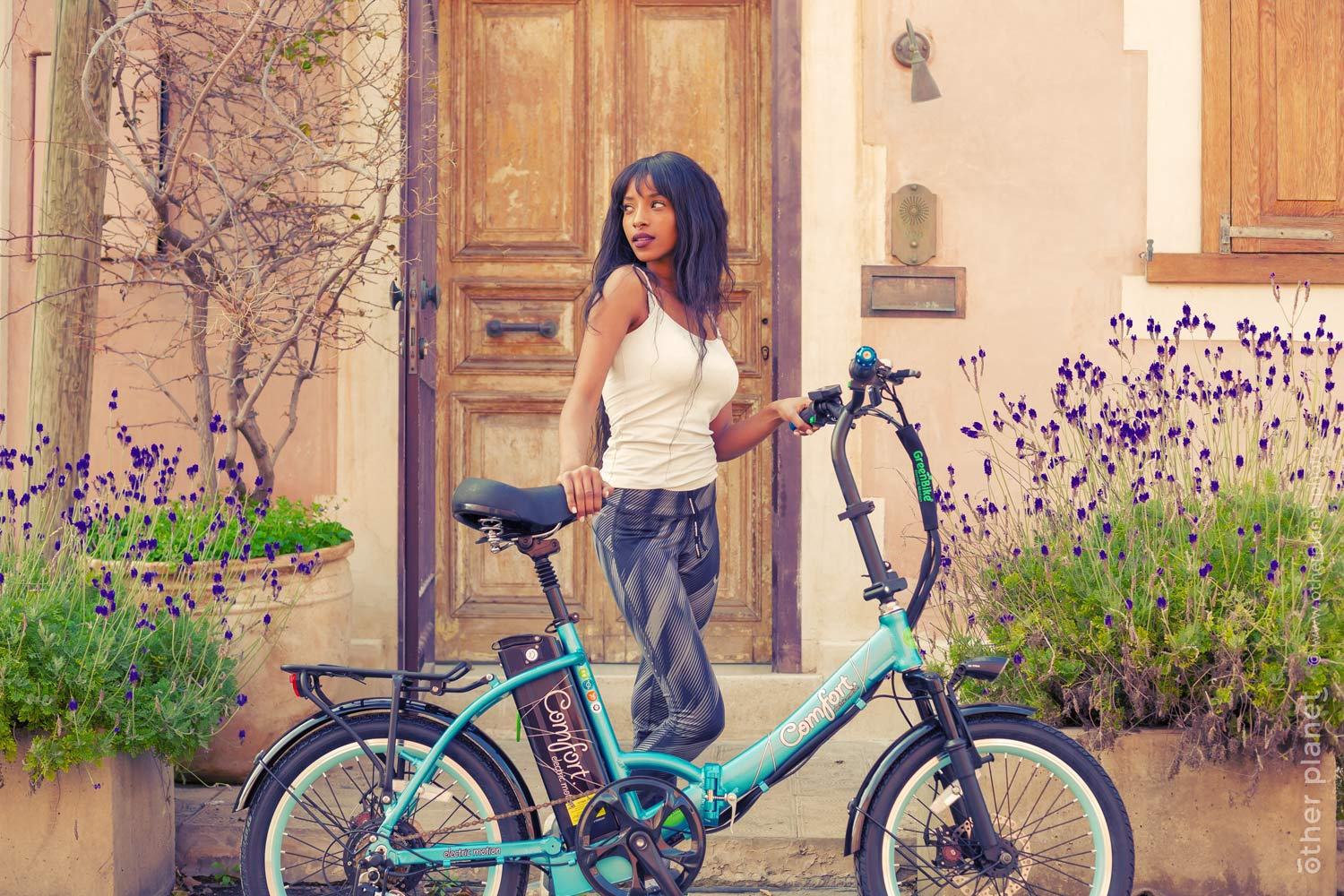 Lifestyle photo of woman standing by e-bike near retro style house