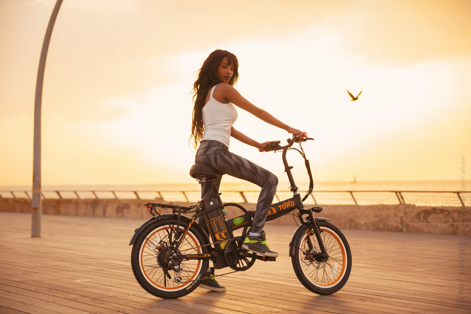 Model riding electric bike by the sea - photo for Greenbike