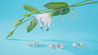 Simple fashion jewelry arrangement with flowers on blue background