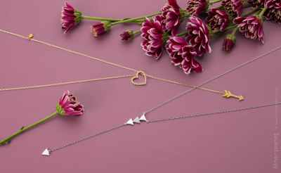 Simple fashion jewelry arrangement with flowers on pink background