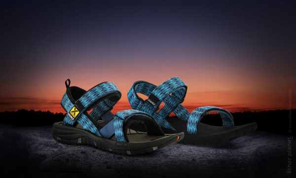 Source hiking sandals on sunset background