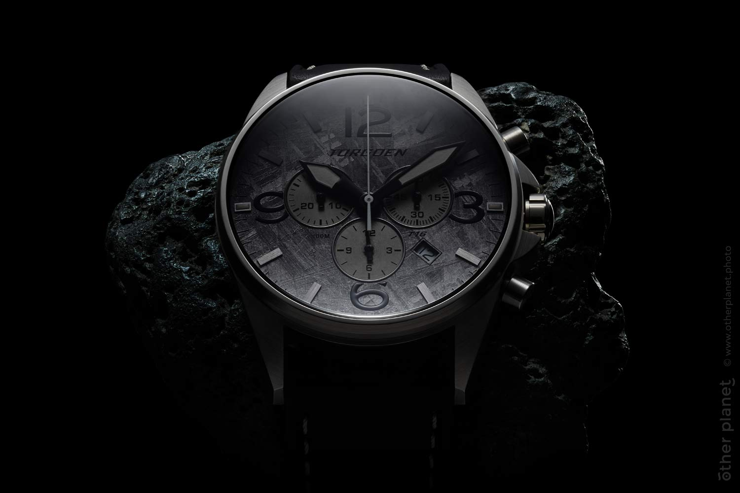 Advertising photo of Torgoen Meteorite Watch with stone on black background