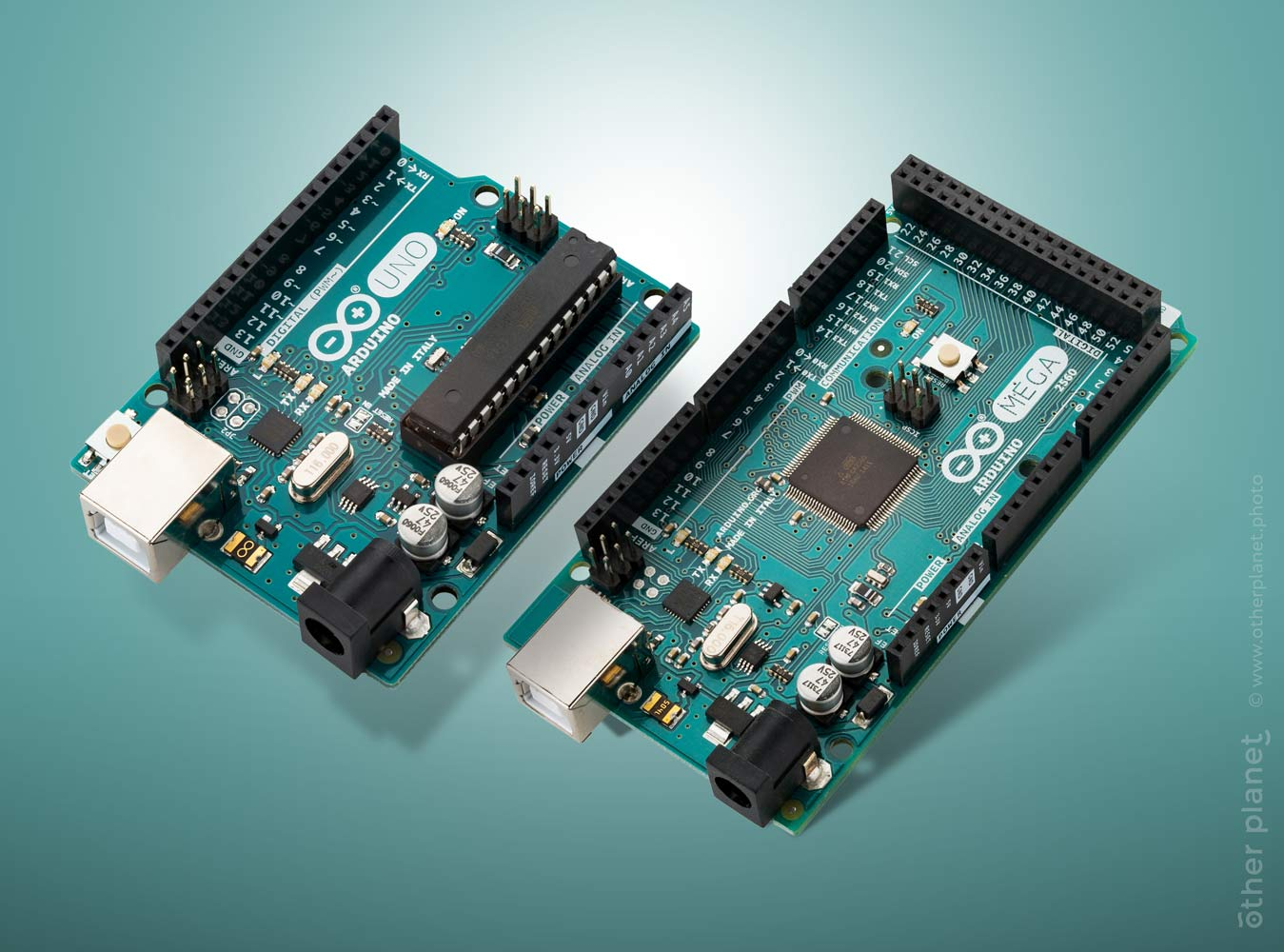 Two Arduino microchips on teal background