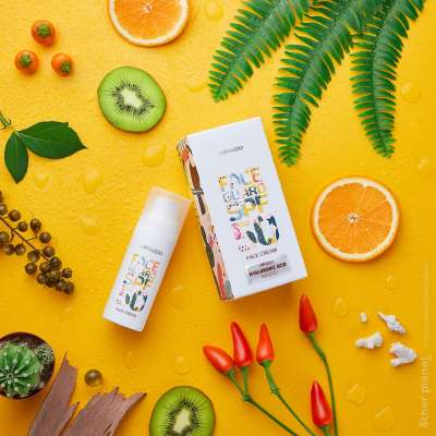 Cosmetics advertising arrangement on yellow background with plants and fruits